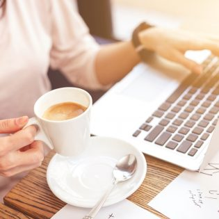 Close up of female hands holding a cup of coffee. Young woman is typing on laptop and sitting at desk